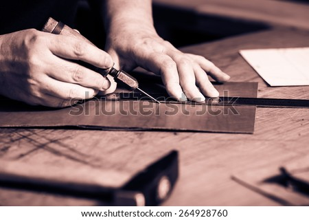 Working process of the leather wallet in the leather workshop. Woman\'s hands holding crafting tool and iron ruler. Monochrome cream tone. Black and white photography.
