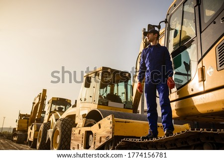 Working process on the construction site. A contractor builder is sitting near excavator. Construction machinery concept Foto stock ©