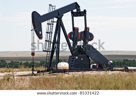 Working pump jack pulling crude oil out of an oil well in Colorado, USA