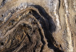Working quarry environment seen from a drone. Amazing colorful patterns created by heavy machinery in the mine. An active quarry at aerial photo from a drone. Aggregate piles and steep quarry walls