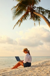 Working remotely on seashore. Young successful woman female freelancer in straw hat working on laptop while sitting on tropical beach at sunset, full length. Distance work concept