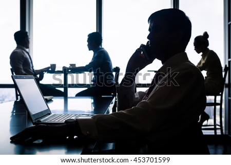 Working situation with employees having coffee, talking and doing business by phone, backlit silhouette shot