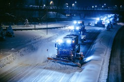 Working snow blowers shine on the road at night, horizontal format