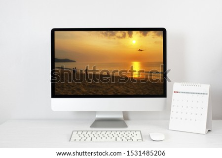 working space and the picture of sunset on the Phuket beach on the mockup desktop computer, calendar and accessories on white desk. holiday concept. clipping path.