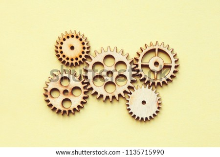 working system of cogwheels, teamwork, flat lay, pastel yellow background