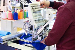 Working technician specialist embroidery industrial machine in sewing workshop