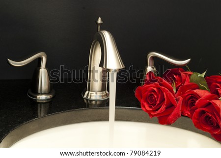 Working water mixer and a few roses on a sink.