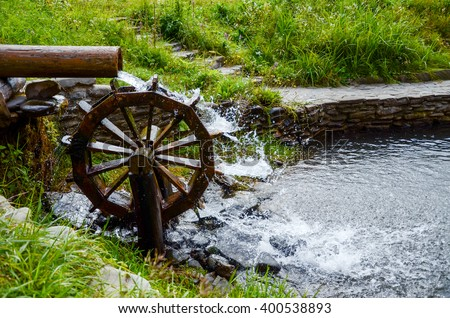 Working watermill wheel with falling water in the village