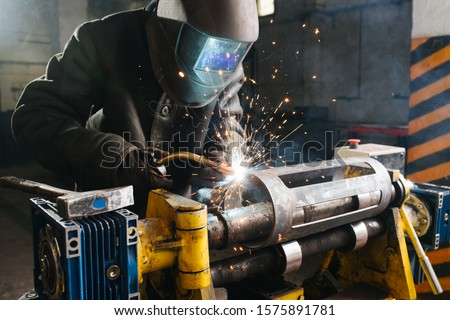 Working welder in protective mask and clothing. He's welding metal piece, fixed with industrial clamp. His mask glowing blue, sparks flying in the air. Workshop is big and resembles hangar.