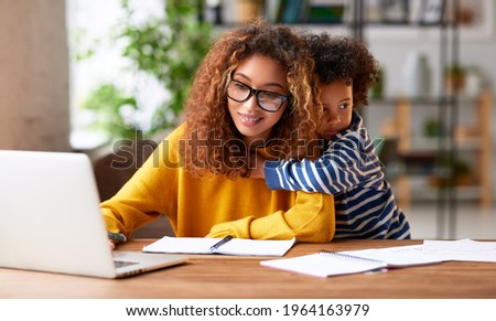 Working with kids. Young focused woman mother wearing eyeglasses using laptop and thinking about work task while small boy son gently hugs her. Childcare concept ストックフォト ©