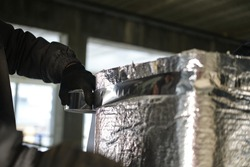 Working with metal tape, insulates the ventilation elements.
