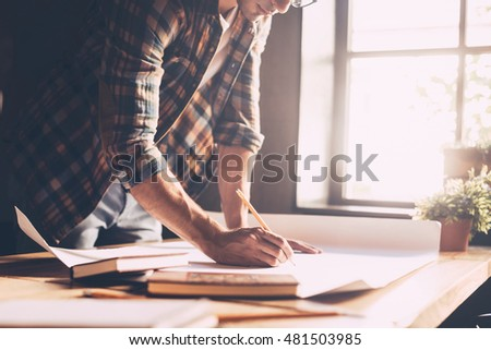 Working with passion. Close-up of confident young man in casual wear sketching on blueprint while standing near wooden desk in creative office