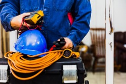 Working with safety protection concept: Electrian engineer holding multimeter and tools in hand, standing behind the heavy duty tool box, image including power cord, Blue hard hat (helmet) and gloves.