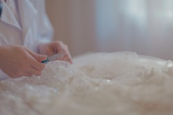 Working with scissors handmade haute-couture, tailoring a wedding dress, high end fashion marriage preparation