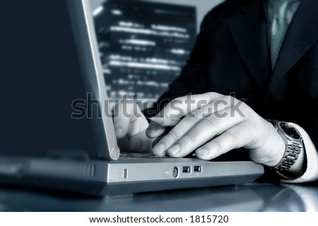 Working with the laptop and a skyscraper in the background