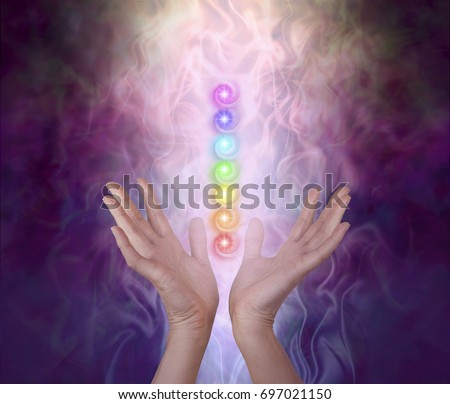 Working with the Seven Major Chakra Energy Vortexes  -  female healer's hands either side of seven chakra vortexes on an ethereal dark to light misty swirling energy field