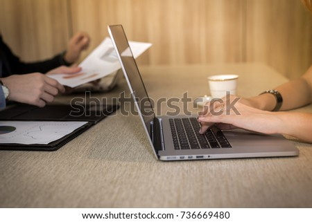 Working woman's hands sitting at a desk typing on her laptop computer in office.