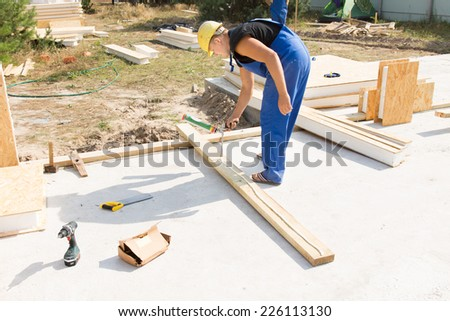 Workman applying wood glue to an insulated wooden beam to be positioned in the corner of the wall on a new build house construction site