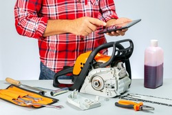 Workman Calculating The Price At Repair Of Chainsaw. Repair of chainsaws,gasoline powered tools. Repairman using digital tablet.