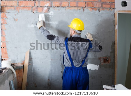 Workman is plastering the wall at the place. #1219113610
