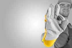 Workman making a perfect gesture with his gloved hand with focus to his hand over a grey background with a highlight and copyspace.