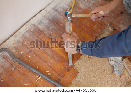 Workman Removing Old Floor Tiles Using A Hammer And Chisel Close Up