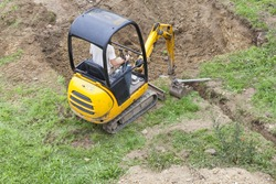 Workman using a mini digger to excavate  a hole for a swimming pool in a garden lawn with green grass viewed from above.