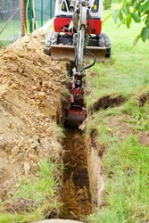 Workman using a mini digger to excavate a hole for water pipes in the garden. Czech republic, Europe.
