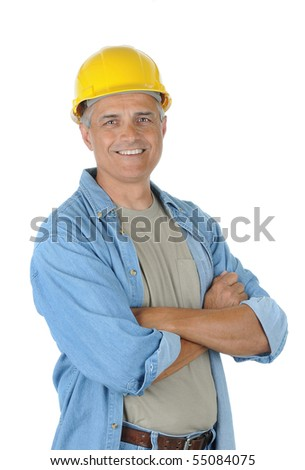 Workman wearing a yellow hard hat and smiling at the camera with his arms crossed. Isolated over white in vertical format.