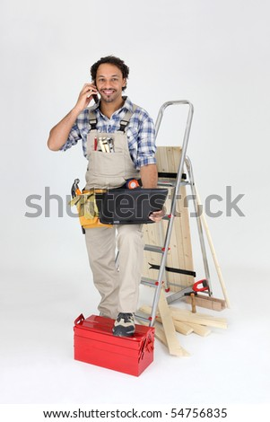 Workman with a laptop computer and a phone on white background