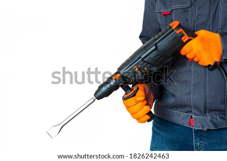 workman with a rotary hammer. isolated Hands in protective gloves with hammer drill perforator. Copy space. isolated Stockfoto ©