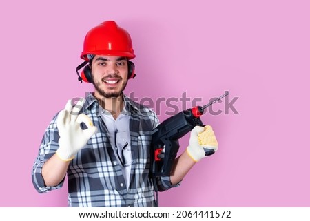Workman with drill, helmet and ear protector, OK sign, on pink background.