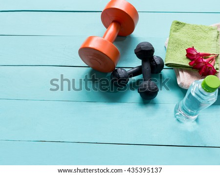 Workout and fitness dieting- Healthy lifestyle concept and other stuff Dumbbell, water, on the blue wooden background