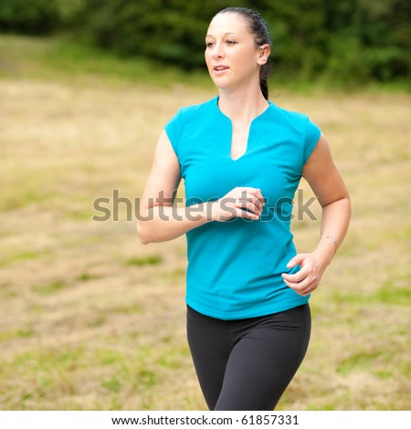 Workout - Cute young active sport girl runs outdoor through forest - stock photo