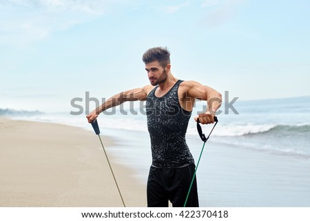 Workout Exercise. Portrait Of Healthy Handsome Active Man With Fit Muscular Body Doing Expander Stretching Exercises, Exercising At Beach. Sporty Male Training Outdoor. Sports And Fitness Concept