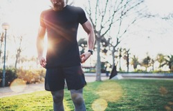 Workout lifestyle concept.Young man preparing muscles before training.Muscular athlete exercising crossfit outside in sunny park. Blurred background