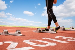 Workout of athlete on start line of cinder-track with numerals of new year on sky background.