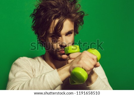 workout of man with barbell or dumbbell, has disheveled and uncombed long hair and beard on face in white underwear on green background, morning exercise and wake up, barbershop, sport