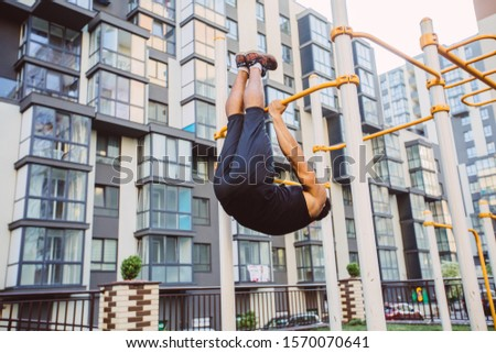 Workout, sportsman pull ups the horizontal bar with big effort. Fitness mixed race man doing workouts in morning on street sports ground outdoors on urban background. Cityscape view