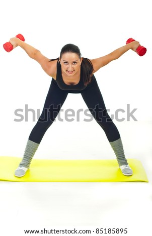 Workout woman with dumbbell standing on yellow mat against white background