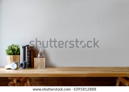 Workplace and copy space with home office supplies on wooden table.