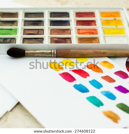 Workplace artist - paper, paint, brushes, color wheel