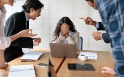 Workplace Conflict And Bullying. Aggressive Coworkers Yelling At Victimized Businesswoman Sitting At Desk In Modern Office. Corporate Communication Problem, Quarrels And Bad Attitude At Work