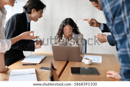 Workplace Conflict And Bullying. Aggressive Coworkers Yelling At Victimized Businesswoman Sitting At Desk In Modern Office. Corporate Communication Problem, Quarrels And Bad Attitude At Work Stock fotó ©