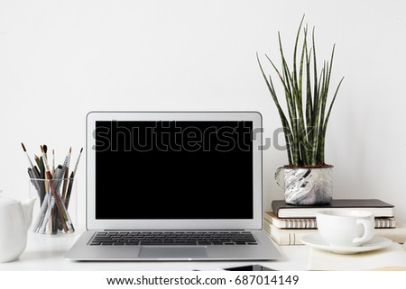 Workplace, gadgets, modern technology and communication. Mock up of open notebook pc, smart phone, office accessories, decorative plant and mug of tea resting on white table with nobody around #687014149