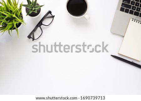 Workplace in office with white desk. Top view from above of laptop with notepad and coffee. Space for modern creative work of designer. Flat lay with blank copy space. Business and finance concept.