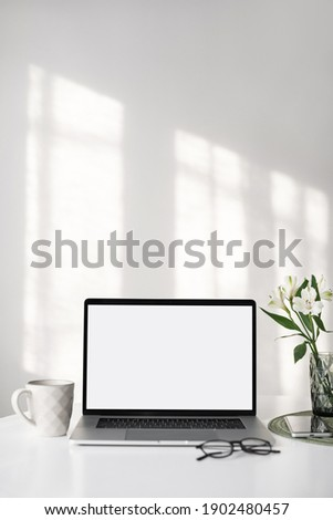 Workplace, laptop computer with blank empty white screen display monitor on desk. Mock up, copy space. Home office concept. Business, working from home, studying, e-learning, web site concept