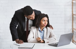Workplace molestation concept. Young African american girl harassed by her lustful boss in office. Panorama