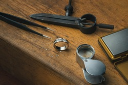 Workplace of a jeweler. Tools and equipment for jewelry work on an antique wooden desktop. Jeweller, engraver at work on jewelry made of diamonds and gold. Wood Platinum Diamond Metal Background