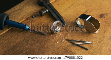 Workplace of a jeweler. Tools and equipment for jewelry work on an antique wooden desktop. Jeweller, engraver at work on jewelry made of diamonds and gold Photo stock ©